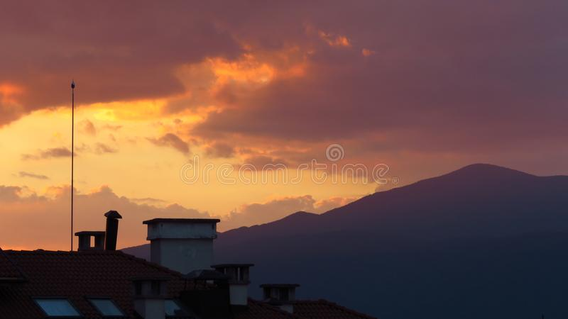 Mooie hemel en kleurrijke wolken in zonsondergangtijd over de bergen en de stad stock fotografie
