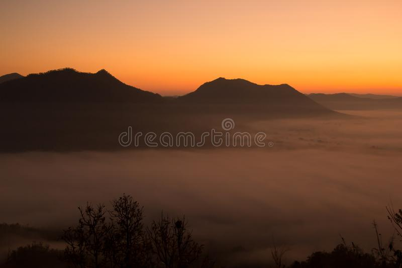 Mooie hemelzonsopgang Berglaag in de straal van de ochtendzon en de wintermist stock fotografie