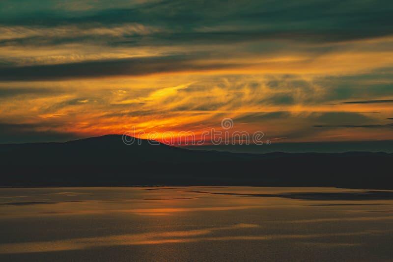 Mooie het branden bewolkte zonsondergang bij het meer met zon gegaan achter de bergen royalty-vrije stock afbeelding
