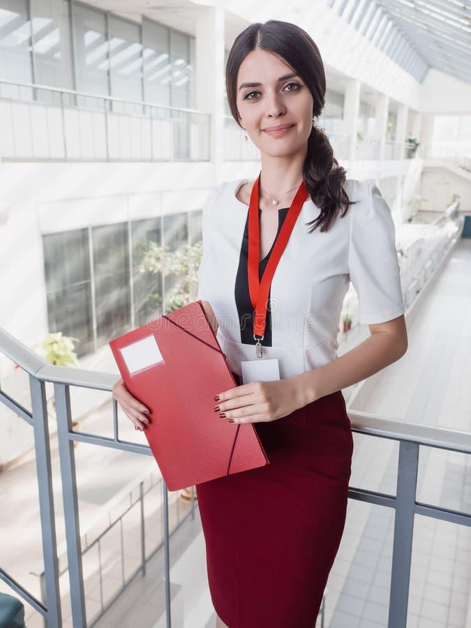 Mooie het Glimlachen de Bureausachtergrond van Onderneemsterstanding against white Portret van Bedrijfsvrouw met een Omslag in Ha royalty-vrije stock fotografie