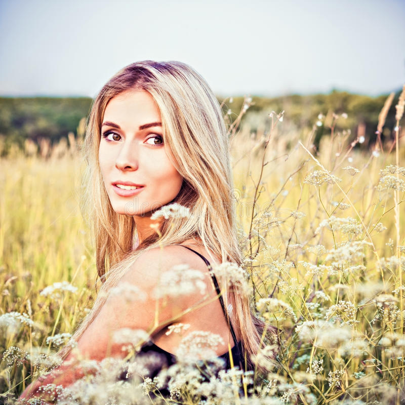 Mooie het glimlachen jonge meisjeszitting onder het gras en de bloemen stock foto's