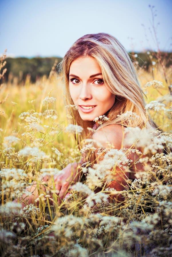 Mooie het glimlachen jonge meisjeszitting onder het gras en de bloemen royalty-vrije stock foto