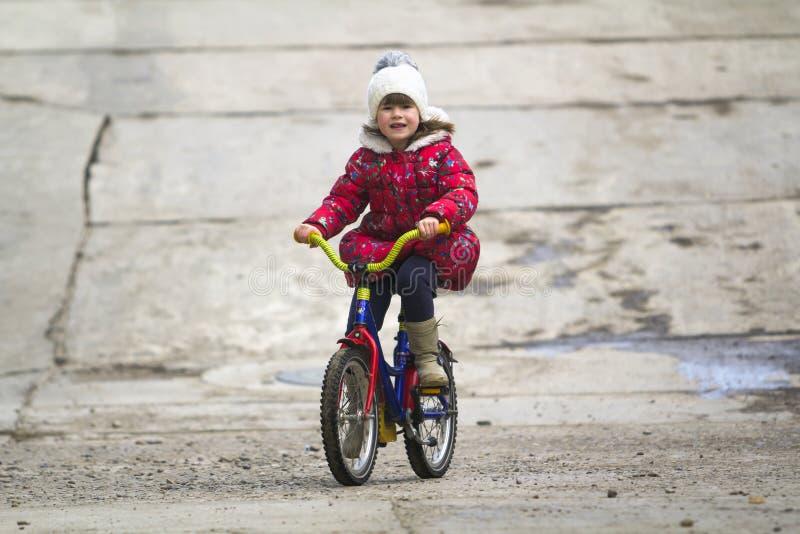 Mooie het glimlachen meisje berijdende fiets in een park stock foto