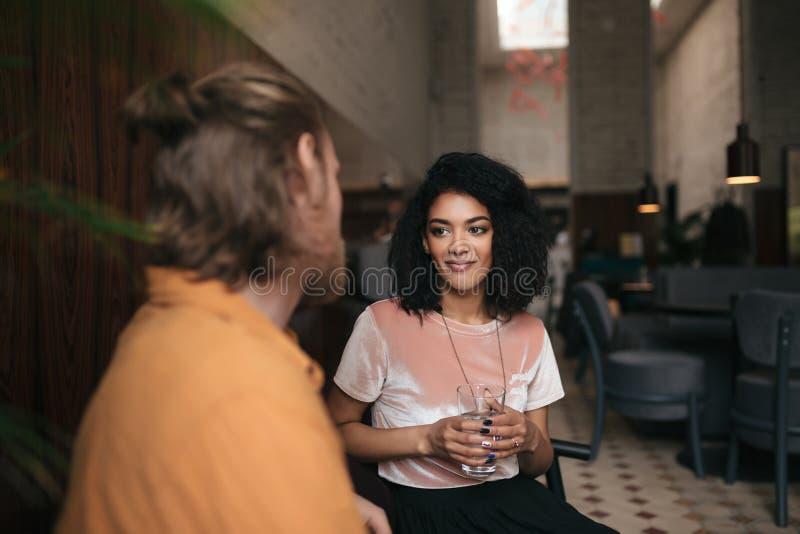 Mooie het glimlachen meisjeszitting in restaurant met vriend Vrij Afrikaanse Amerikaanse damezitting bij koffie met glas van royalty-vrije stock foto