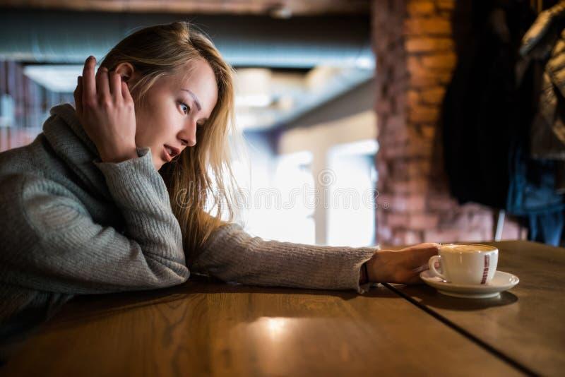 Mooie het glimlachen vrouw het drinken koffie bij koffie Portret van rijpe vrouw in een cafetaria die hete cappuccino drinken en  royalty-vrije stock afbeeldingen