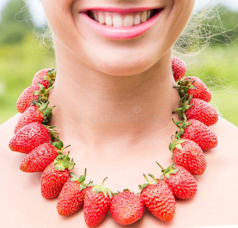 Mooie het glimlachen vrouwenhals met rode die parels van verse aardbei worden gemaakt stock afbeelding