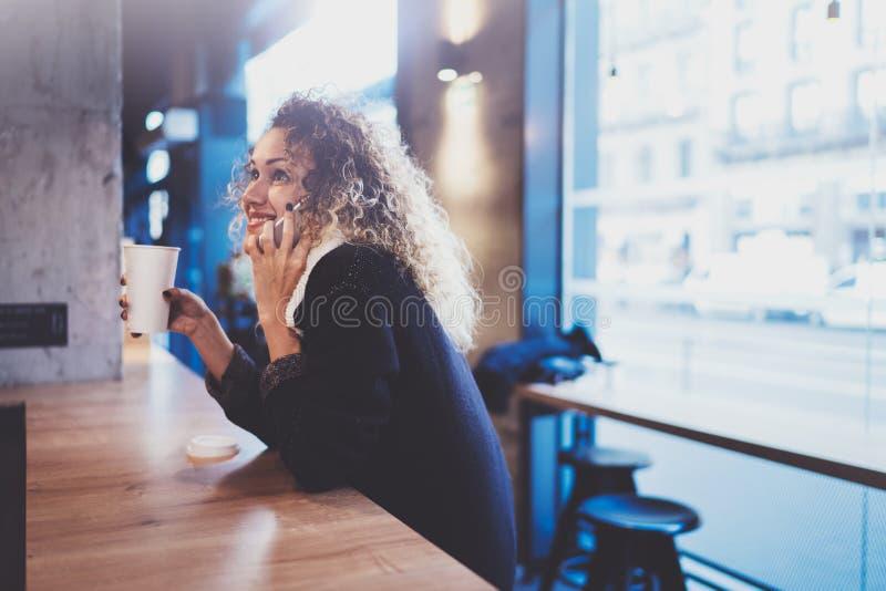Mooie het glimlachen vrouwenzitting bij stedelijke koffie en het spreken met vrienden via mobiele smartphone Toevallig portret va royalty-vrije stock foto