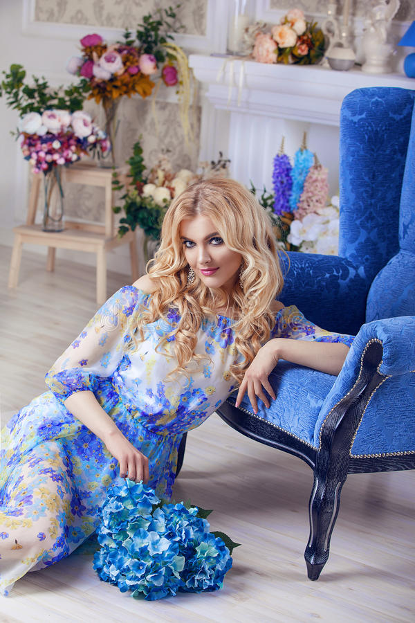 Mooie het portret professionele makiyad en het haar van de meisjes modelvrouw in een bloem kleden zich op een bloemenachtergrond, royalty-vrije stock afbeelding