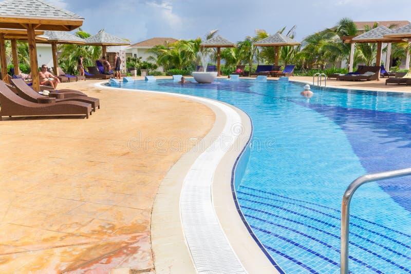 Mooie het uitnodigen mening van comfortabel comfortabel gebogen zwembad met mensen die, en van hun tijd ontspannen zwemmen geniet royalty-vrije stock foto