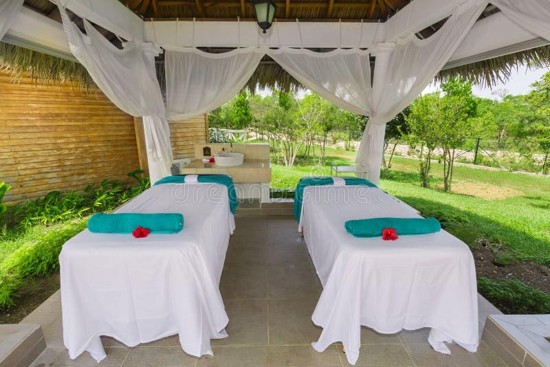 Mooie het uitnodigen mening van comfortabele comfortabele massagebedden die zich binnen gazebo in tropische tuin bevinden royalty-vrije stock fotografie