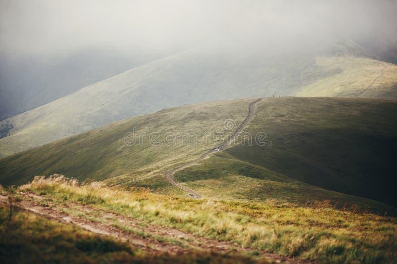 Mooie heuvel en weg in mistige zonnige bergen landschap landsc stock fotografie