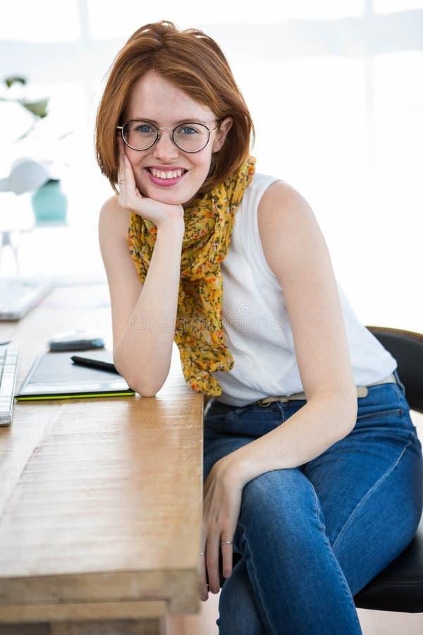 mooie hipster bedrijfsvrouw die op haar bureau leunen stock afbeeldingen