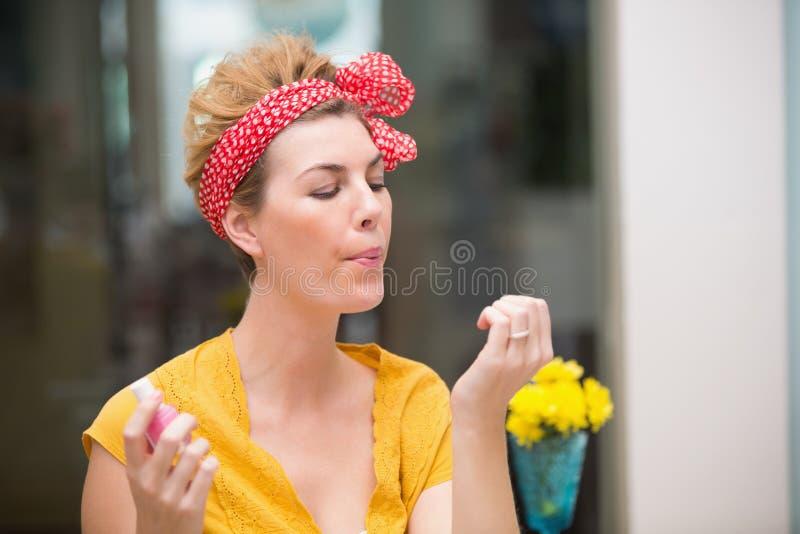 Mooie hipster die op haar natte spijkers blazen stock foto