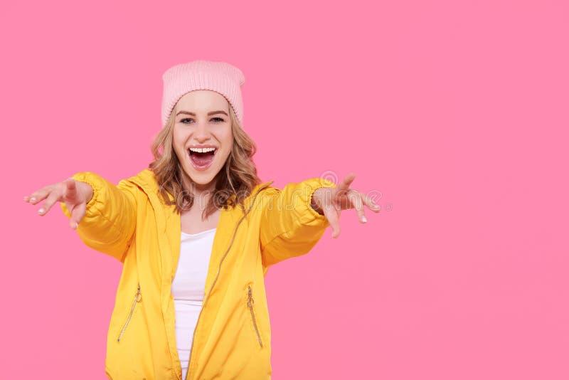 Mooie hipstertiener in helder geel jasje en roze super opgewekt van de beaniehoed Het koele jonge portret van de vrouwenmanier royalty-vrije stock afbeelding