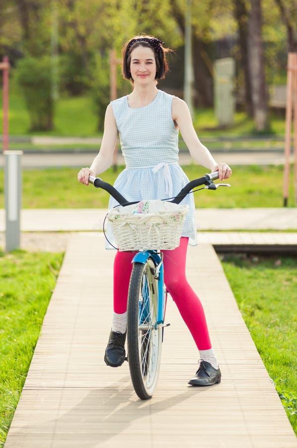 Mooie hipstervrouw op fiets in het park stock afbeelding