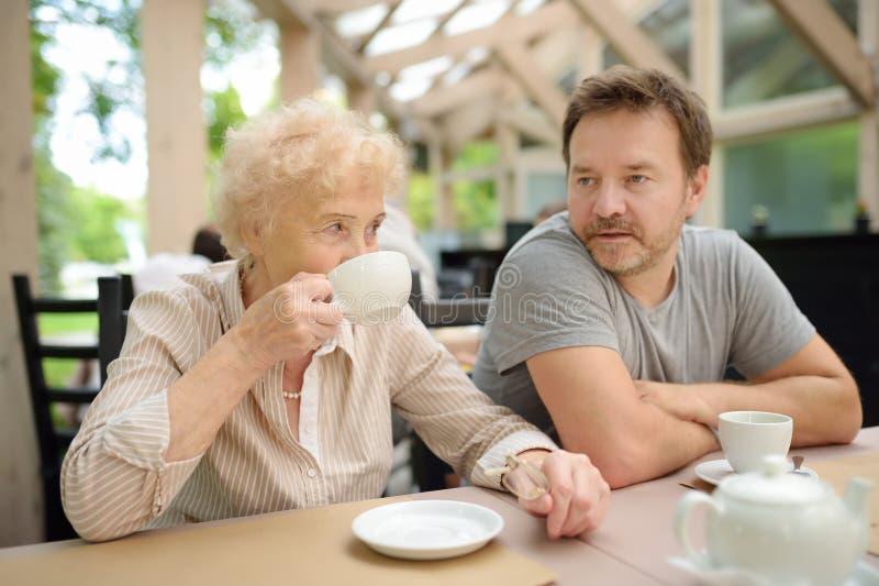 Mooie hogere dame met zijn rijpe zoon het drinken thee in in openlucht koffie of restaurant Bejaarde damelevensstijl stock afbeelding