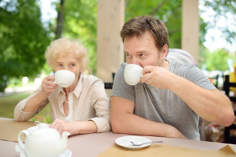 Mooie hogere dame met zijn rijpe zoon het drinken thee in in openlucht koffie of restaurant Bejaarde damelevensstijl stock foto's