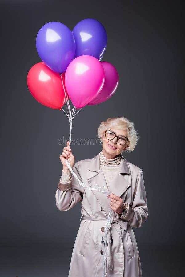 mooie hogere dame in trenchcoat en oogglazen die ballons houden, royalty-vrije stock foto