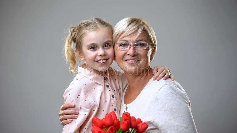 Mooie hogere de bloemengift van de dameholding van kleindochter en het koesteren, liefde stock afbeelding