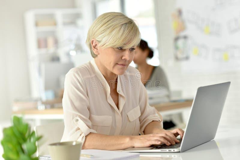 Mooie hogere vrouw die aan laptop op kantoor werken stock afbeeldingen