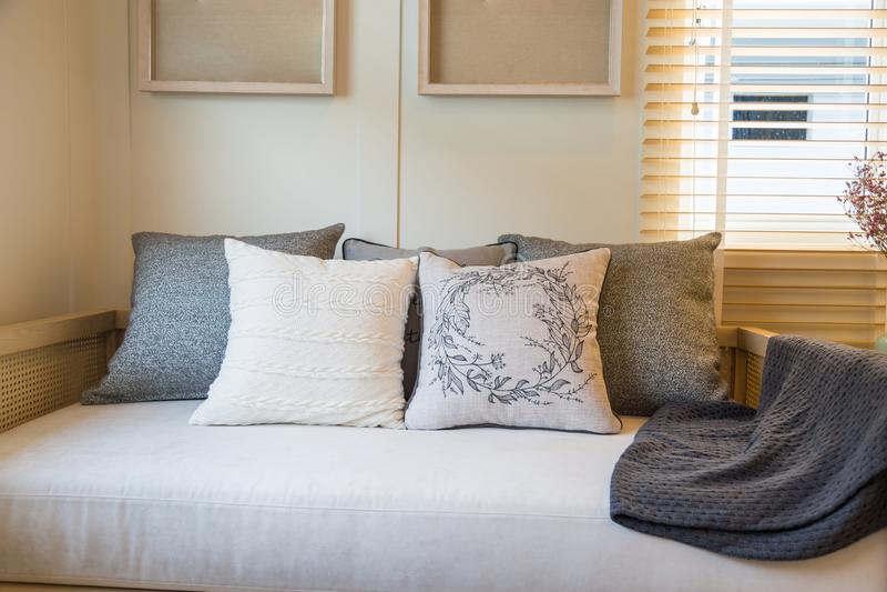 Mooie hoofdkussens op beige stoffenbank in woonkamer stock foto