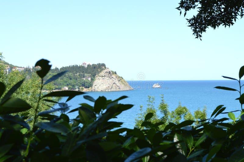 Mooie hoogste die mening van de kust van de Zwarte Zee, en de bergen in de Krim door bladeren van bomen wordt ontworpen stock foto