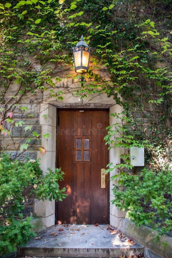 Mooie houten die deur door groene klimop met wijnoogst aangestoken lantaarn wordt behandeld stock foto's