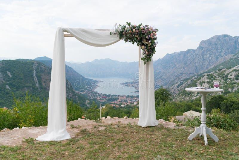 Mooie houten die huwelijksboog met bloemen wordt verfraaid royalty-vrije stock afbeeldingen