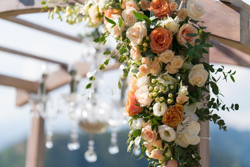 Mooie houten die huwelijksboog met bloemen wordt verfraaid stock foto