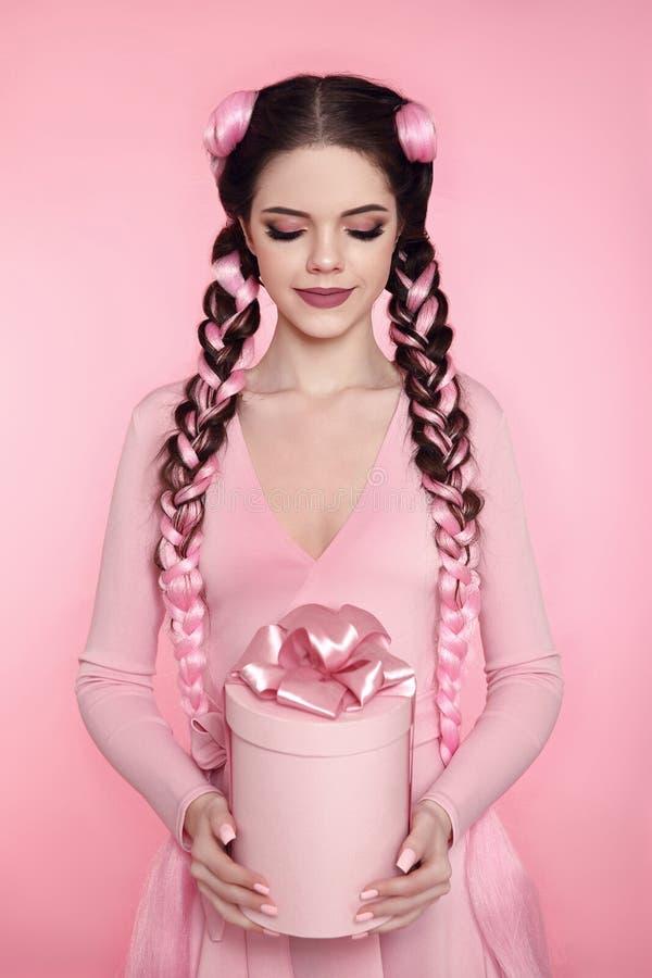 Mooie mooie huidige de giftdoos van het tienermeisje met boog over roze s stock foto