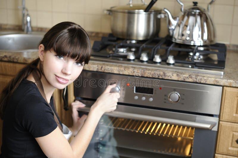 Mooie huisvrouw die de oven schakelt royalty-vrije stock foto