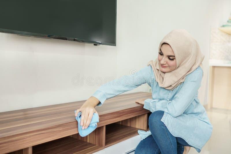 Mooie huisvrouw die hijab schoonmakend haar huis dragen royalty-vrije stock fotografie