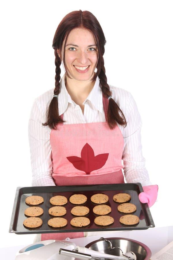 Mooie huisvrouw die met cakes pronkt stock foto's