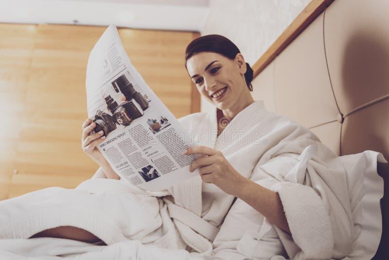 Mooie huisvrouw die verse pers lezen royalty-vrije stock fotografie