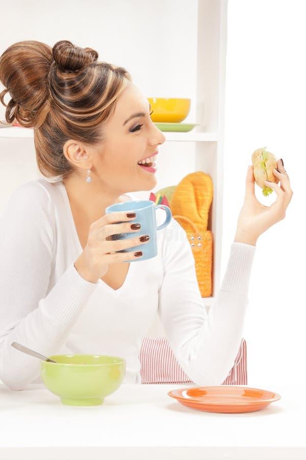 Mooie huisvrouw met sandwich stock foto