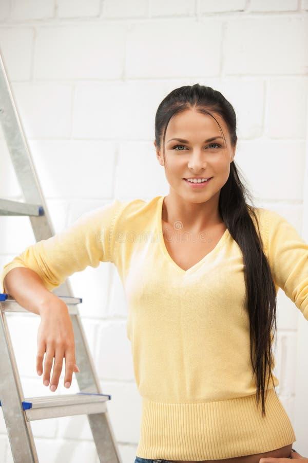 Mooie huisvrouw met stapladder stock afbeeldingen