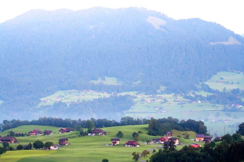 Mooie huizen in de Zwitserse bergvallei bij dageraad stock foto