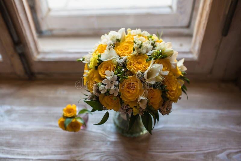 Mooie huwelijksboeket en bruidegom boutonniere op vensterbankachtergrond royalty-vrije stock foto