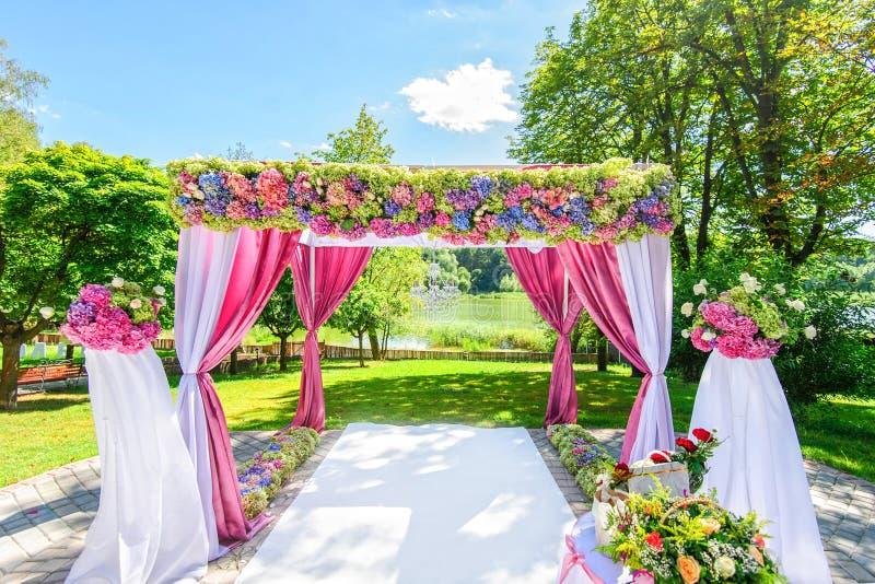 Mooie huwelijksboog met bloemen in tuin stock foto