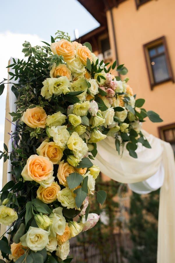 Mooie huwelijksboog met verse bloemen in beige kleuren in de tuin stock foto's