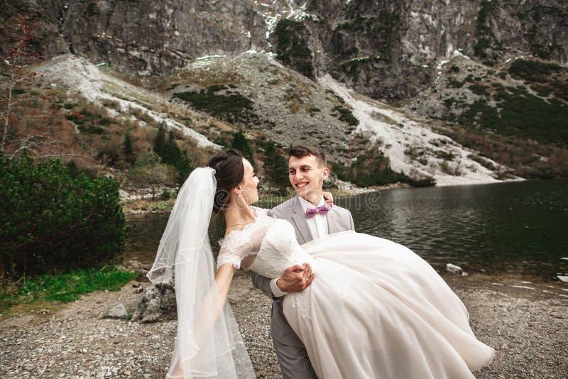 Mooie huwelijksphotosession De bruidegom omcirkelt zijn jonge bruid, op de kust van het meer Morskie Oko polen royalty-vrije stock afbeeldingen