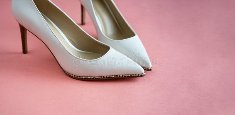Mooie huwelijksschoenen op een hoge en dunne gouden stiletto De luxueuze schoenen van het ontwerperhuwelijk op een roze lijst stock afbeelding