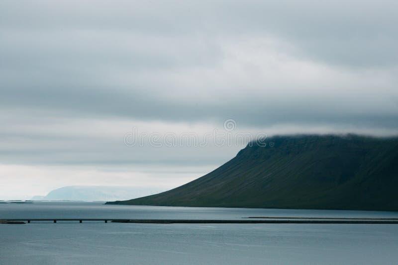 mooie Ijslandse zeekust met bergen en brug stock afbeeldingen