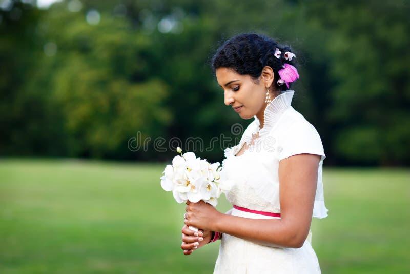 Mooie Indische bruid in de zomerpark De gelukkige jonge bloemen van de vrouwenholding Meisje na huwelijk, geluk en nieuwe familie royalty-vrije stock afbeeldingen
