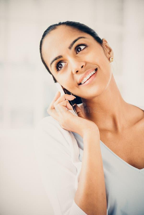 Mooie Indische vrouw die mobiele gelukkige telefoon met behulp van stock afbeelding