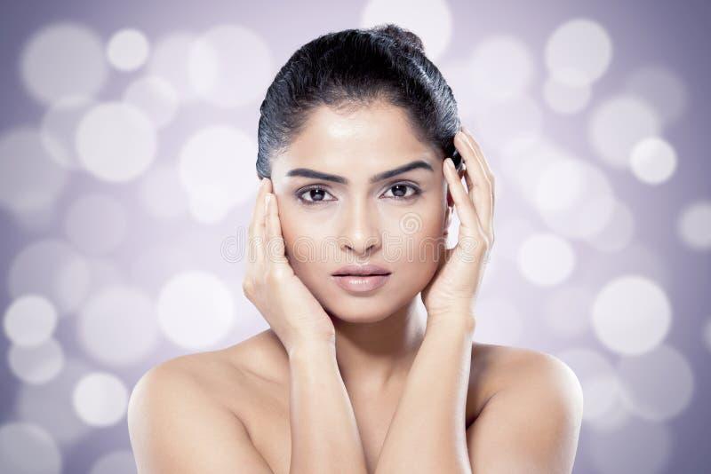 Mooie Indische vrouw met gezonde huid tegen vage lichtenachtergrond royalty-vrije stock afbeelding