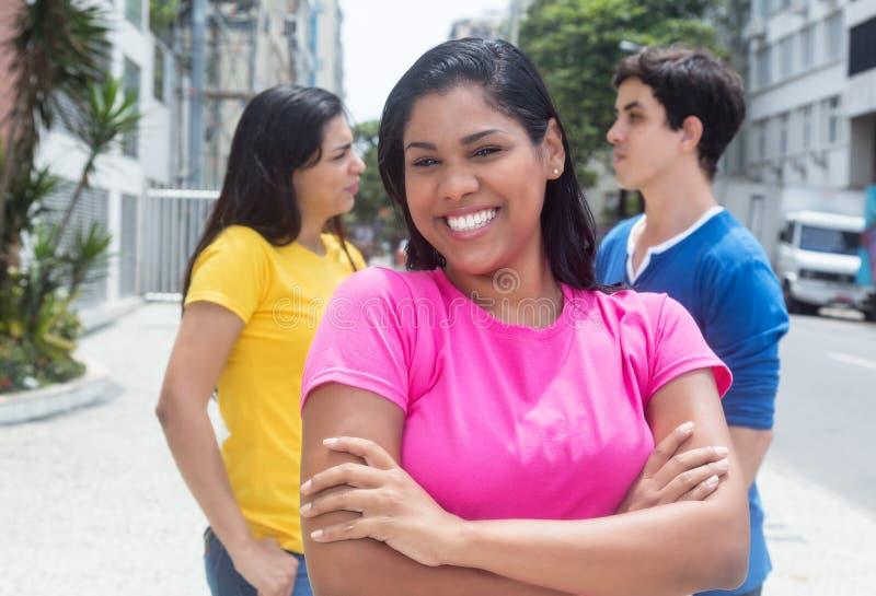 Mooie inheemse Latijnse student met vrienden in openlucht stock afbeeldingen