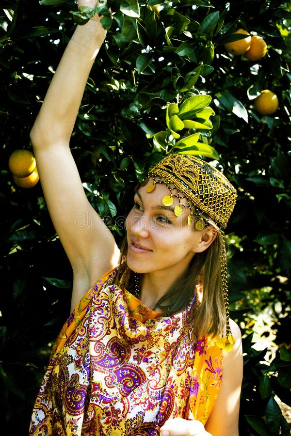 Mooie islam vrouw die in oranje bosje, echt moslimmeisje che glimlachen stock foto