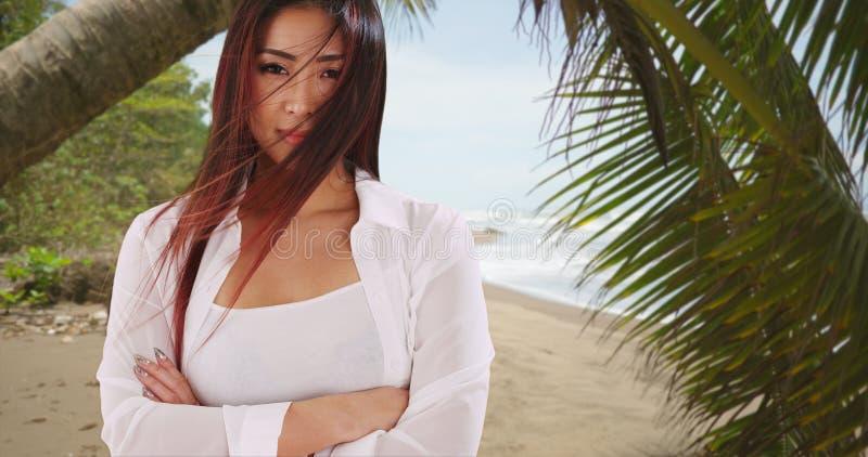 Mooie Japanse vrouw die zich bij het strand bevinden die bij camera glimlachen royalty-vrije stock afbeeldingen