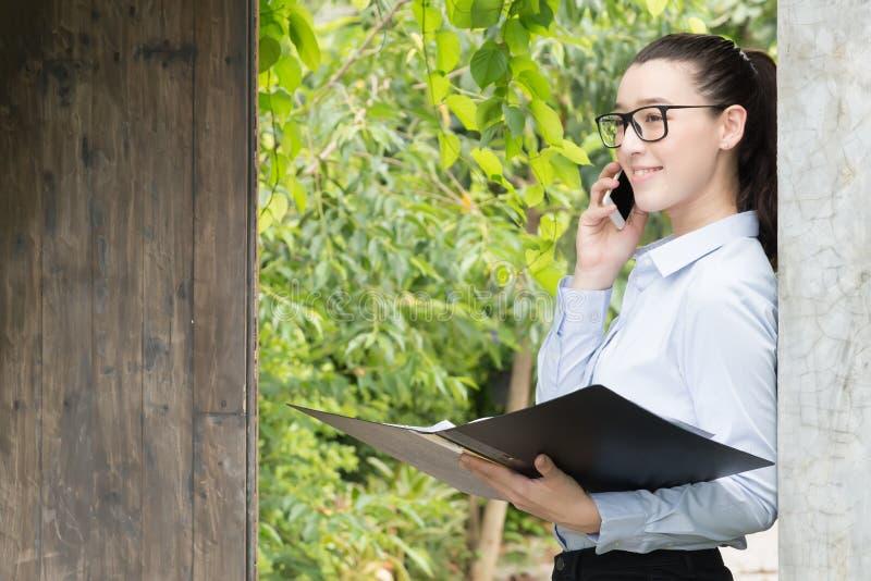 Mooie jonge aantrekkelijke bedrijfsvrouw die haar smartphonecommunicatie met haar klant gebruiken De gelukkige smartphone van het royalty-vrije stock foto's